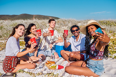 Buy stock photo Shot of a group of young friends taking selfies and having a picnic together at the beach