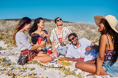Buy stock photo Shot of a group of young friends taking pictures and having a picnic together at the beach