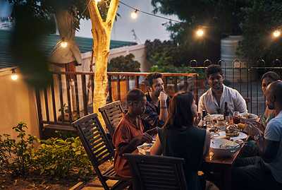 Buy stock photo Shot of a group of young friends having a dinner party outdoors
