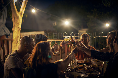 Buy stock photo Shot of a group of young friends toasting with drinks at a dinner party outdoors