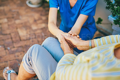 Buy stock photo Cropped shot of an unrecognizable female nurse consoling a senior woman outdoors at a nursing home