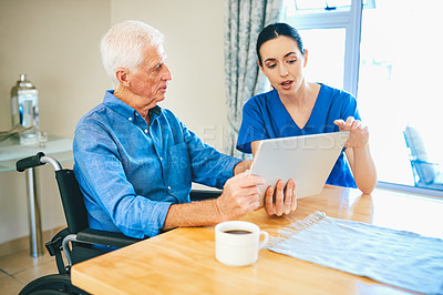 Buy stock photo Cropped shot of a senior man and a female nurse using a digital tablet together in a nursing home