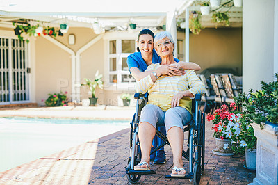 Buy stock photo Full length portrait of an attractive young female nurse embracing a senior woman outdoors at a nursing home