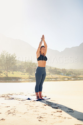 Buy stock photo Shot of a beautiful young woman practising yoga on the beach