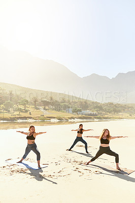 Buy stock photo Shot of three young women practicing yoga on the beach