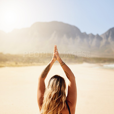 Buy stock photo Rearview shot of a young woman practising yoga on the beach