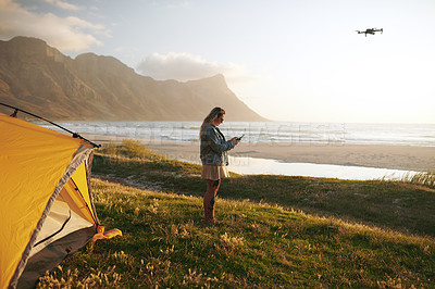 Buy stock photo Full length shot of an attractive young woman flying a drone while camping  outdoors by herself near the beach