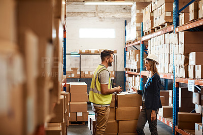 Buy stock photo Shot of a young man and woman having a discussion while working together in a warehouse