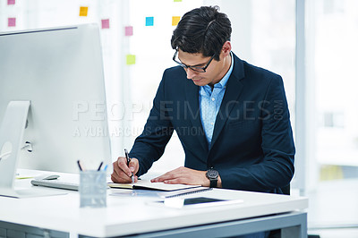 Buy stock photo Shot of a young businessman writing notes in an office