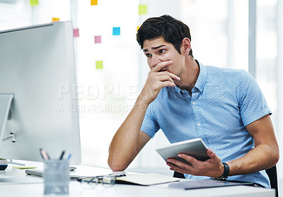 Buy stock photo Shot of a young businessman looking concerned while working in an office