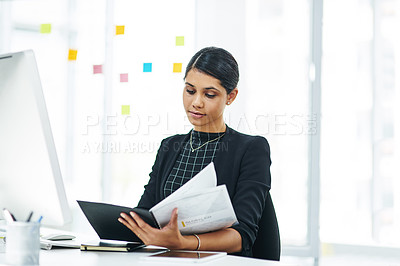 Buy stock photo Shot of a young businesswoman going through a folder in an office