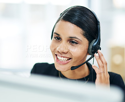 Buy stock photo Shot of a young businesswoman using a headset while working on a computer in an office