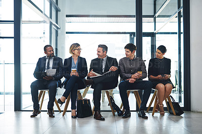 Buy stock photo Full length shot of a diverse group of businesspeople sitting in line for an interview in a modern office