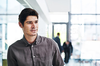 Buy stock photo Cropped shot of a handsome young businessman looking thoughtful in a modern office with his colleagues in the background