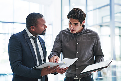 Buy stock photo Cropped shot of two young businessmen having a discussion while standing in a modern office