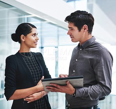 Buy stock photo Cropped shot of two young businesspeople a digital tablet while standing together in a modern office