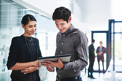 Buy stock photo Cropped shot of two young businesspeople using a digital tablet in an office with colleagues in the background