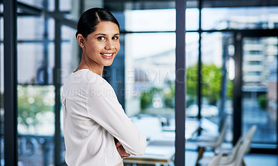 Buy stock photo Cropped portrait of an attractive young businesswoman smiling while standing with her arms folded in a modern office
