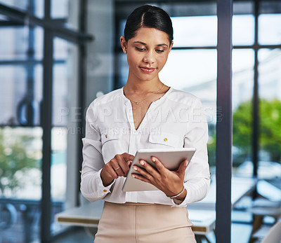 Buy stock photo Cropped shot of an attractive young businesswoman using a digital tablet while standing in a modern office