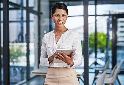 Buy stock photo Cropped portrait of an attractive young businesswoman smiling while using a digital tablet in a modern office