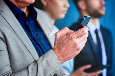 Buy stock photo Cropped shot of an unrecognizable businessman standing with his colleagues and using his cellphone
