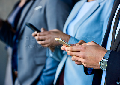 Buy stock photo Cropped shot of an unrecognizable businesswoman standing with her colleagues and using her cellphone