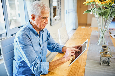 Buy stock photo Shot of a happy senior man using a digital tablet while relaxing alone at home