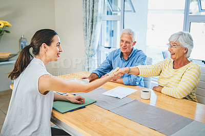 Buy stock photo Shot of a happy senior couple agreeing and shaking hands with their financial advisor at home