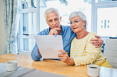 Buy stock photo Shot of a senior couple going through paperwork and planning their finances together at home