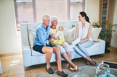 Buy stock photo Full length shot of a happy senior couple going over paperwork with their financial advisor at home
