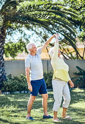 Buy stock photo Shot of a happy senior couple dancing together in their backyard at home