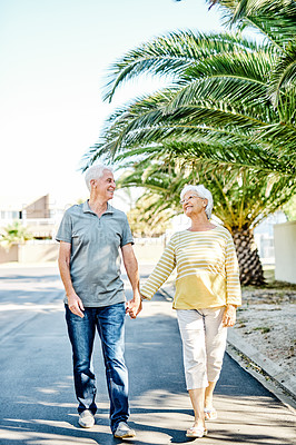 Buy stock photo Shot of a happy senior couple going for a leisurely walk down the street in their neighbourhood