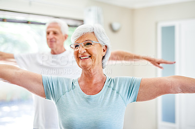 Buy stock photo Shot of a senior woman exercising with her husband indoors
