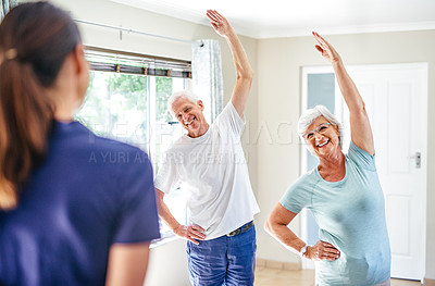 Buy stock photo Shot of a senior couple exercising with an instructor indoors