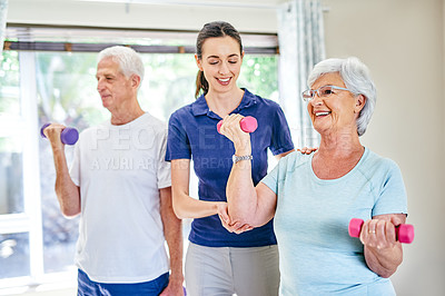 Buy stock photo Shot of an instructor assisting a senior couple with weightlifting exercises in a fitness class