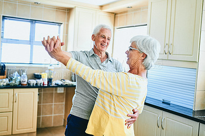 Buy stock photo Cropped shot of a senior couple slow dancing in their kitchen at home