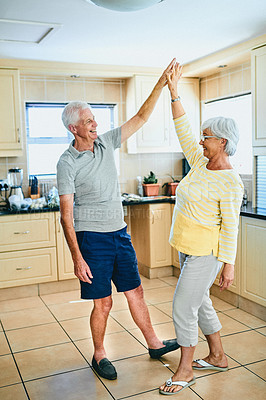 Buy stock photo Shot of a senior couple slow dancing in their kitchen at home