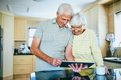Buy stock photo Cropped shot of a senior couple using a digital tablet while standing in the kitchen at home