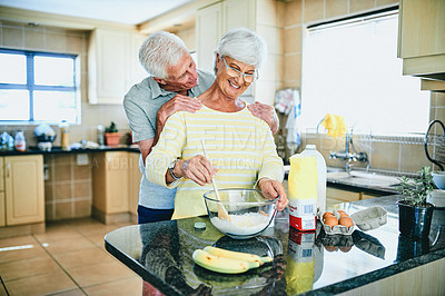 Buy stock photo Shot of a senior man standing behind his wife while baking