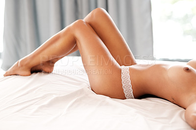Buy stock photo Cropped shot of an unrecognizable woman lying topless on her bed at home