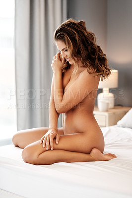 Buy stock photo Full length shot of a gorgeous young woman smiling while sitting naked on her bed at home