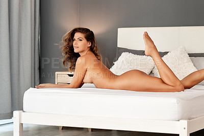 Buy stock photo Cropped shot of a gorgeous young woman lying naked on her bed at home
