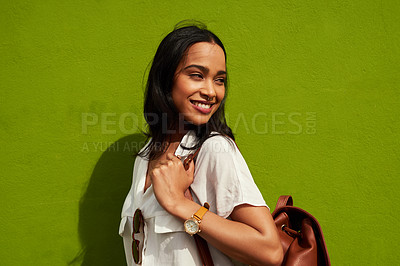 Buy stock photo Cropped shot of an attractive young woman standing alone against a green background during a day out in the city
