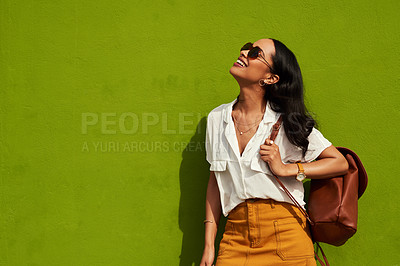 Buy stock photo Cropped shot of an attractive young woman wearing sunglasses while standing alone against a green background in the city