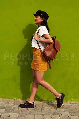 Buy stock photo Full length shot of an attractive young woman walking against a green background during a day out in the city