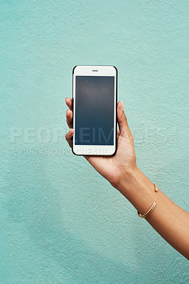Buy stock photo Cropped shot of an unrecognizable woman holding her cellphone against a blue background in the city