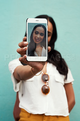 Buy stock photo Cropped portrait of an attractive young woman standing and using her cellphone to take a selfie against a blue background