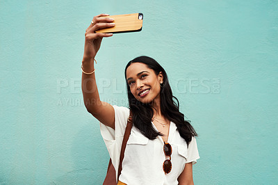 Buy stock photo Cropped shot of an attractive young woman standing and using her cellphone to take a selfie against a blue background