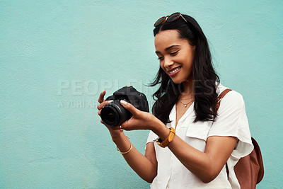 Buy stock photo Cropped shot of an attractive young woman standing alone against a blue background in the city and holding her camera