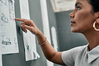 Buy stock photo Closeup shot of an architect working with blueprints on a wall in an office
